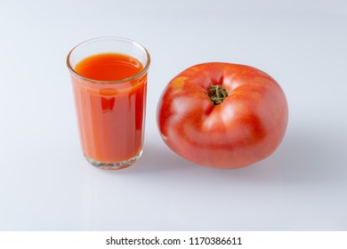 Large tomato and a glass of tomato juice