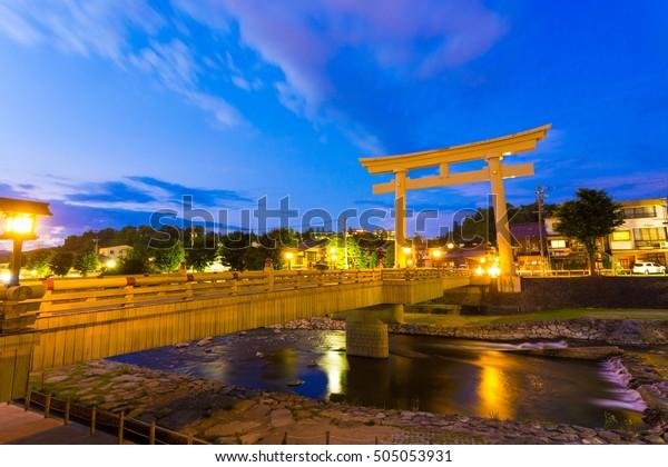 Large torii gate stands at end of Miyamae-bashi bridge spanning Miya-gawa river during blue hour at dusk in Hida-Takayama, Gifu Prefecture, Japan