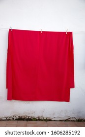 large towel hanging on a washing line against a wall