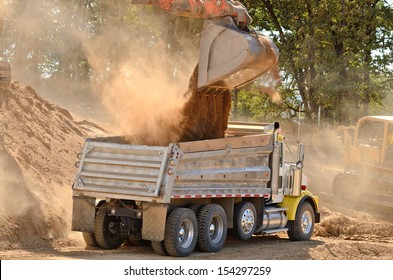 Large track hoe excavator filling a dump truck with rock and soil for fill for a new commercial development road construction project