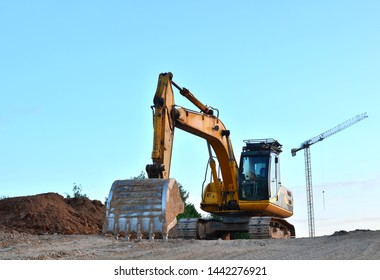 Large tracked excavator digs the ground for the foundation and construction of a new building in the city. Road repair, asphalt replacement, renovating a section of a highway, bridge construction