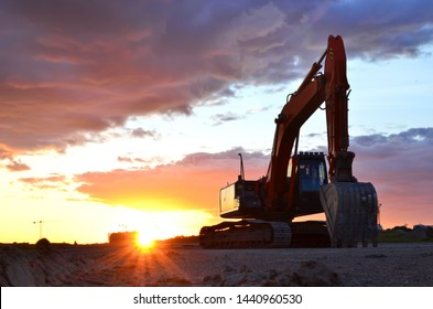 Large tracked excavator on a construction site against the background of the  awesome sunset. Road repair, asphalt replacement. Small roughness sharpness, possible granularity  - Image