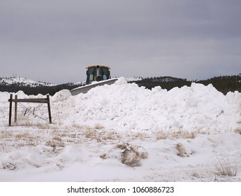 Large tractor clears snow on rural road