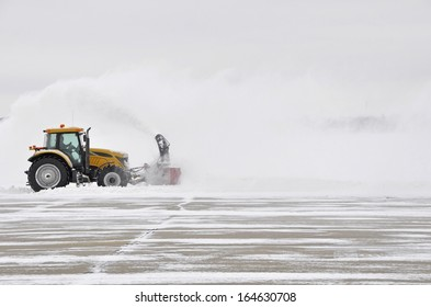 large tractor with snow plow at work during a winter storm