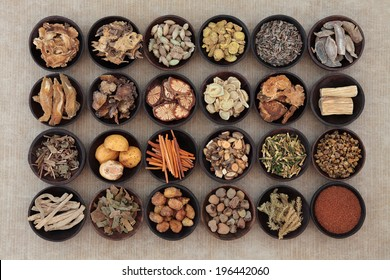 Large traditional chinese herbal medicine selection in wooden bowls.