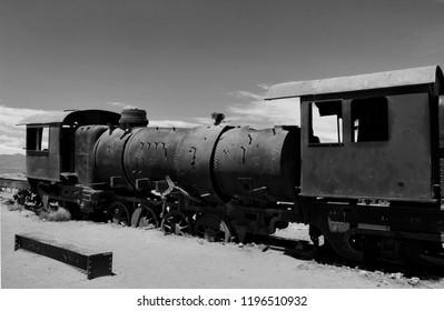 Large train graveyard, black and white landscape photo of metal cemetery and locomotive, Uyuni, Bolivia