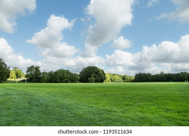 Large trimmed green grass soccer field with beautiful cloudy blue sky and copy space