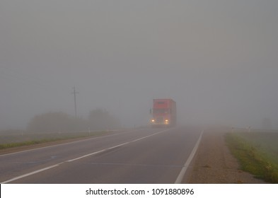 A large truck is driving along the summer road in the morning in a thick fog