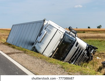 The large truck lies in a side ditch after the road accident.