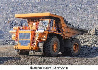 A large truck loaded with iron ore rides in a quarry