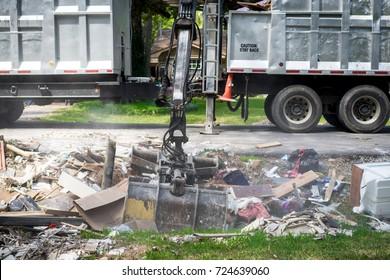 Large truck picking up trash and debris outside of neighborhoods devastated by Hurricane Harvey