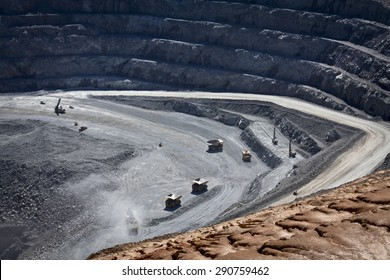 Large trucks being filled with ore at the bottom of an open cast mine. Barrick Cowal Gold Mine in New South Wales, Australia.