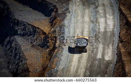 Large trucks transport gold ore from open cast mine. Gold Mine in New South Wales, Australia.