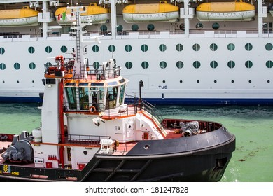 A large tugboat by a white luxury cruise ship