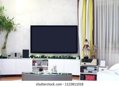 Large TV inside modern living room interior decorated with Christmas lights and ornaments