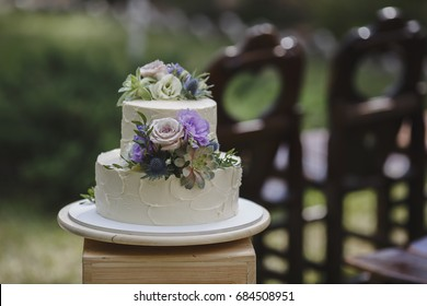 A large two-tiered cake decorated with fruit and fresh flowers. The composition of flowers, fruits and berries. Trendy wedding cake.