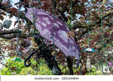 Large umbrella decorated with clouds, and many small ornaments of cats, dogs and other animals embellish a tree in a front yard of a Seattle home.