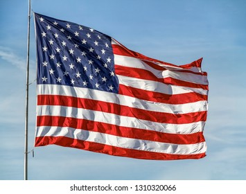 A large United States Flag flies proudly against a cloudy blue sky.