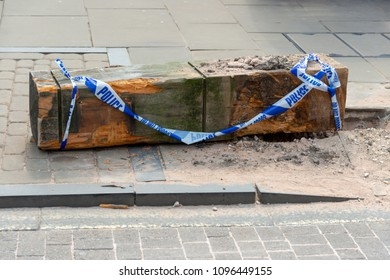 large uprooted and vandalised wooden post on pavement sidewalk in street covered in police do not cross blue tape