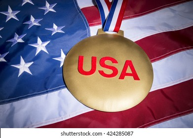Large USA gold medal with red, white, and blue ribbon on textured stars and stripes of American flag