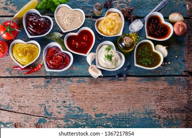 Large variety of marinades, sauces, herbs and spices with a decanter of olive oil in individual heart shaped bowls on a rustic wood background with copy space, top down view