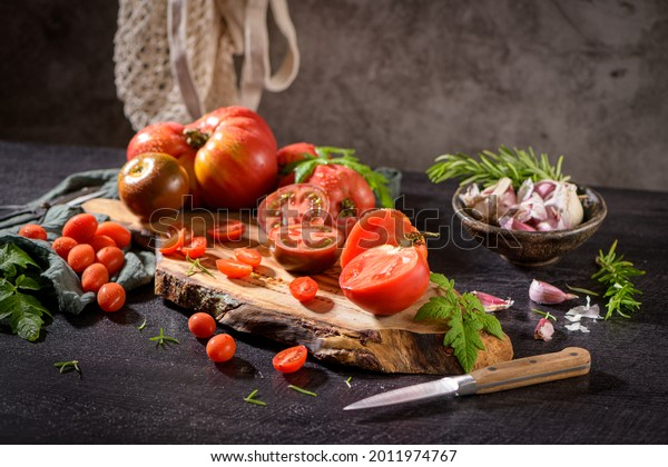 Large variety of tomatoes on rustic kitchen counter. Preparation of tomato sauce.