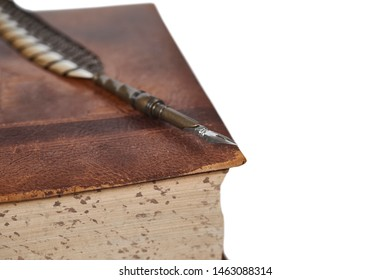 Large vintage book covered in leather  with a quill pen laying on top of it isolated on white with shallow depth of field