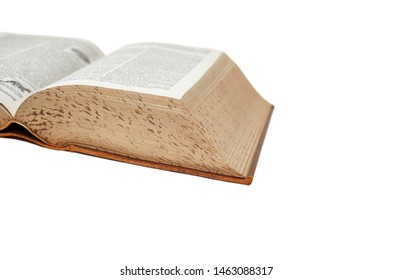 Large vintage dictionary covered in leather laying open isolated on white with shallow depth of field