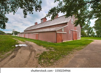 A large, vintage styled barn and stable combination sits on a farm