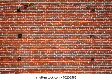 Large wall of old red bricks with  rusted steel reinforcement supports