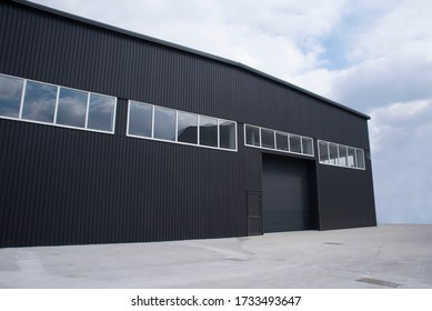 Large warehouse exterior with sheet metal and automatic gate