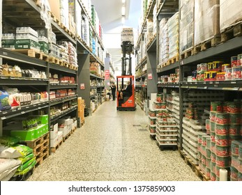 Large warehouse wholesale with rows of aisles and shelves from floor to ceiling. Forklift lifting boxes to the upper shelves. Copenhagen, Denmark - April 19, 2019.