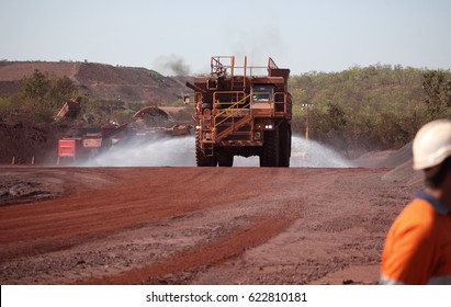 A large water truck drives along spraying a red mine haul road.