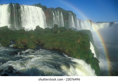 Large waterfalls with white water falling over cliff. Green vegitation and rainbow. Iguacu Falls, Brazil.