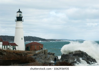 Large waves break overjagged rocks by Portland head lighthouse in Maine on a cloudy day in late winter season. Tourists look onward.