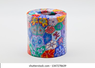 Large wax candle decorated with abstract designs of many colors, isolated on a white limbo background