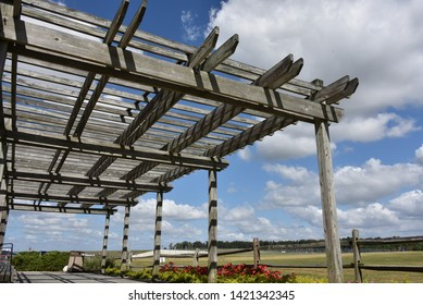 A large, weathered, wooden pergola opens to  blue cloud skies and a field of green grass. Scenic landscape on a beautiful summer day at the park.
