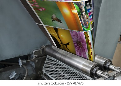 Large webset offset printing press running a long roll off paper over its rollers at high speed.