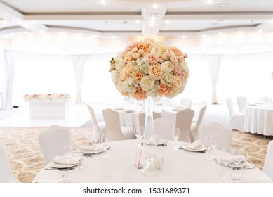 A large wedding bouquet of an assortment of fresh roses of pastel shades adorns the festive table