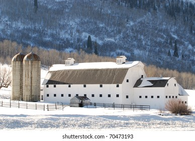 Large white barn in the mountains near Park City, Utah during winter.