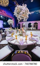 Large white bouquets of roses stand on dinner tables decorated with golden glasses and violet cloth