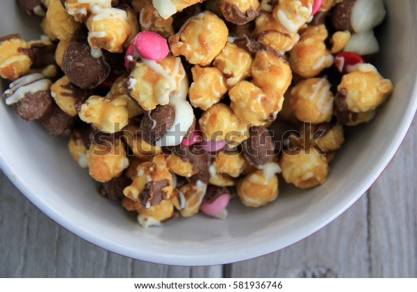 Large white bowl filled with popcorn and candy