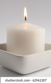Large white candle in a square tray close up