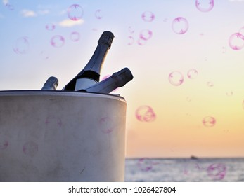 Large, white champagne cooler with three champagne bottles inside directly in front of the Atlantic Ocean and the evening sky, delicate pink soap bubbles float through the air, an atmospheric image,