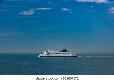 A large white ferry on the ocean on a sunny day with blue sky