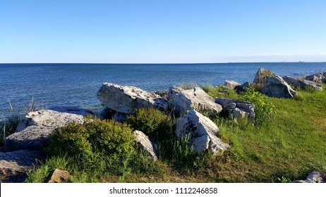 Large white granite stones & vegitation overlooking the Great Lake Michigan shoreline with a city and clouds in the distance.  Captured on a sunny afternoon in the upper Midwest. Spring/ Summer, 2017