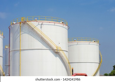 large white Industrial tanks for petrol and oil with blue sky.Fuel tanks at the tank farm. metal stairs on the side of an industrial chemical container.Staircase on big fuel tank