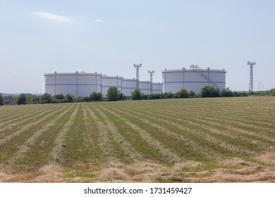 large white Industrial tanks for petrol and oil - panoramic view. Мetal stairs on the side of an industrial chemical container. Staircase on big fuel tank.