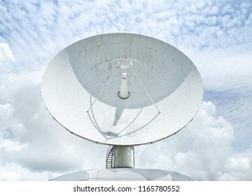 large white satellite dish turn up skyward on blue sky in earth communication antenna system center station