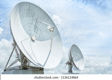 large white satellite dishes turn up skyward on blue sky in earth communication antenna system center station